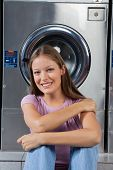 Portrait of beautiful young woman sitting against washing machine in laundromat