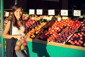Woman buying fruits and vegetables at farmers market. Candid portrait of young woman shopping for he