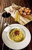 Italian traditional recipe, spaghetti alla carbonara with ingredients on background and a glass of r