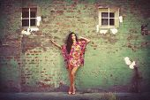 woman in colorful summer dress lean on old brick wall outdoor shot summer day