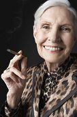 Closeup portrait of an elegant senior woman smoking cigarillo against black background
