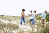 Happy little friends playing ring around the rosy on a grassy beach