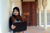 stock photo of muslimah  - Young asian muslim woman in head scarf smile with laptop - JPG