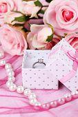 Rose en verlovingsring op roze doek
