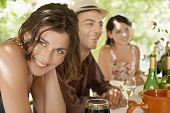 Retrato de mujer joven hermosa con amigos disfrutando de bebidas en fiesta