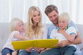stock photo of short-story  - Happy family reading a story together on the couch - JPG