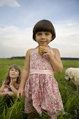 Little Cute Girl With Cracker Standing In The Middle Meadow