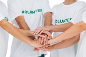 Group of volunteers putting hands together on white background