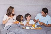 Family having breakfast together in bed