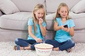 Twins eating popcorn and watching television sitting on a carpet