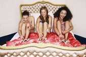 stock photo of slumber party  - Three teenage girls in pajamas painting toenails on funky bed at slumber party - JPG