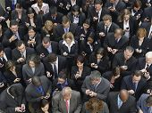 Elevated view of large group of business people text messaging with mobile phones