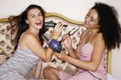 Teenage girls playing with brushes and hair dryer at slumber party