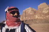 Closeup of an Arab man in turban wearing Sunglasses in desert landscape