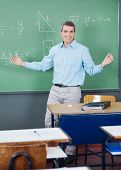 Portrait of mature professor standing arms outstretched against board in classroom