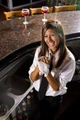 image of bartender  - Hispanic female bartender drying hands behind the bar - JPG