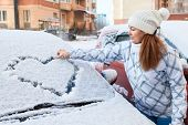 Pretty Woman In The Winter Clothes Drawing Heart On Car