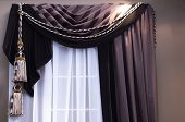 stock photo of swag  - brown swag curtains with tassels on window with sheers - JPG