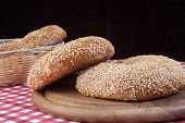 pic of bagel  - Round Sesame Bagels in basket on red table and black background - JPG