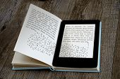 stock photo of understanding  - modern ebook reader on book on wooden background - JPG