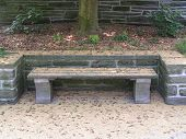 stock photo of fieldstone-wall  - Wooden bench covered in pollen from a nearby holly tree - JPG