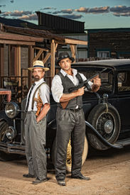 pic of tommy-gun  - 1920s era criminal partners with guns outdoors  - JPG