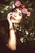 young beautiful woman portrait with wreath of flowers in field summer day retro colors