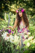 beautiful young woman summer portrait with wreath of flowers in hair and basket of flowers in hand
