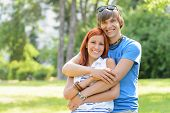 Teenage couple hugging in sunny park smiling at camera