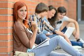 Young studying woman with friends sitting on ground outside college