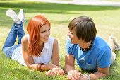 Teenage couple lying on grass looking at each other sunny