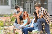 Student friends sitting on bench outside university campus laughing chatting