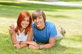 Teenage couple lying on grass summer love smiling at camera