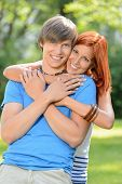 Young loving couple teenagers embracing and smiling in sunny park