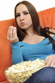 young woman eat popcorn, watching movies and eat popcorn at modern home living room  isolated on whi