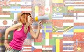Redhead Girl Shouting With A Megaphone Over Flags Background