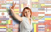 Young Woman Doing Victory Gesture Over Flags Background
