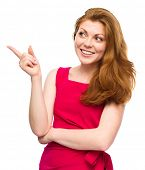 Portrait of a young woman pointing to the left using her index finger, isolated over white