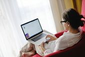 happy young woman relaxing at home and using laptop