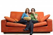 female friends eating popcorn and watching tv at home on orange sofa isolated on white