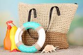 Summer wicker bag with accessories on sand, on nature background