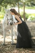 Beautiful Woman Outdoors With a White Horse