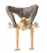 stock photo of upside  - circus gymnast woman flexible body standing on arms upside down balancing balls on feet - JPG