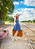 Beautiful woman with blue dress and suitcase on a train station. Serbia.