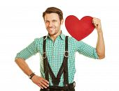 Man in bavaria holding a big red heart on his shoulder