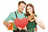 Happy couple with red heart and beer at Oktoberfest in Bavaria