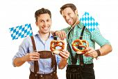 Two smiling men holding a pretzel and a bavarian flag