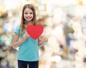 love, happiness and people concept - smiling little girl with red heart