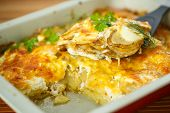 stock photo of baked potato  - new potatoes baked with cheese in baking dish - JPG