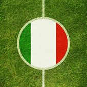 Football field center closeup with Italian flag in circle